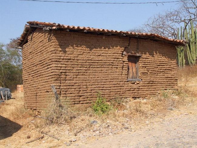 Antes de irse el hijo promete que esa casa de tierra va a ser de de ladrillo.